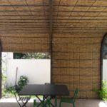 Couverture d'une pergolas arrondie en fer forgé par des paillassons de 1,5 x 5.