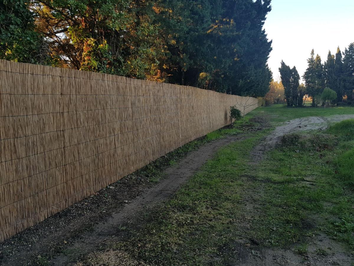 Réalisation d'une clôture en limite de parcelle. La structure grillage est recouverte d'une seule épaisseur de paillasson, d'une hauteur de 2m.